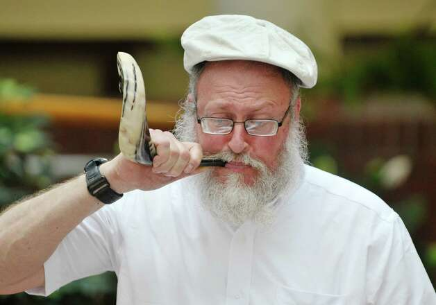 Leible Morrison, president of the Beth-Tephilah Synagogue, blows into a shofar at the OTo LifeO Festival put on by the synagogue at the Troy Atrium on Sunday, Aug. 23, 2015, in Troy, N.Y.  The event featured Jewish ethnic foods, music and talks on the religion and culture.    (Paul Buckowski / Times Union) Photo: PAUL BUCKOWSKI / 00033019A