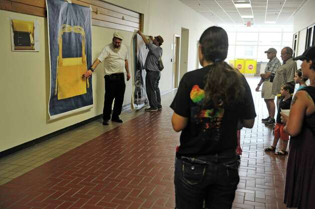 Leible Morrison, background left, president of the Beth-Tephilah Synagogue, gestures towards a painting of the ark of the covenant on the wall as he talks about the Jewish faith at the OTo LifeO Festival put on by the synagogue at the Troy Atrium on Sunday, Aug. 23, 2015, in Troy, N.Y.  The event featured Jewish ethnic foods, music and talks on the religion and culture.    (Paul Buckowski / Times Union) Photo: PAUL BUCKOWSKI / 00033019A