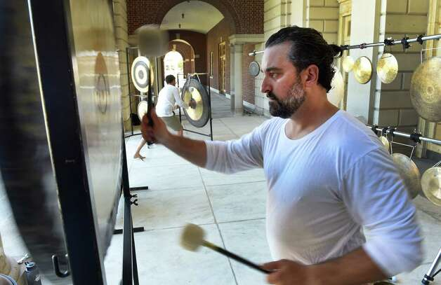 Jim Pavoldi plays a gong in concert with his brother Nick, background, at the gong bath at the Roosevelt II Bath House at the Saratoga State Park  Aug. 23, 2015 in Saratoga Springs, N.Y.      (Skip Dickstein/Times Union) Photo: SKIP DICKSTEIN / 00033077A