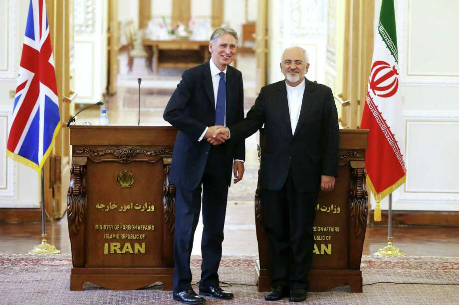 British Foreign Secretary Philip Hammond (left) and his Iranian counterpart, Moham- mad Javad Zarif, shake hands. Photo: Ebrahim Noroozi /Associated Press / AP