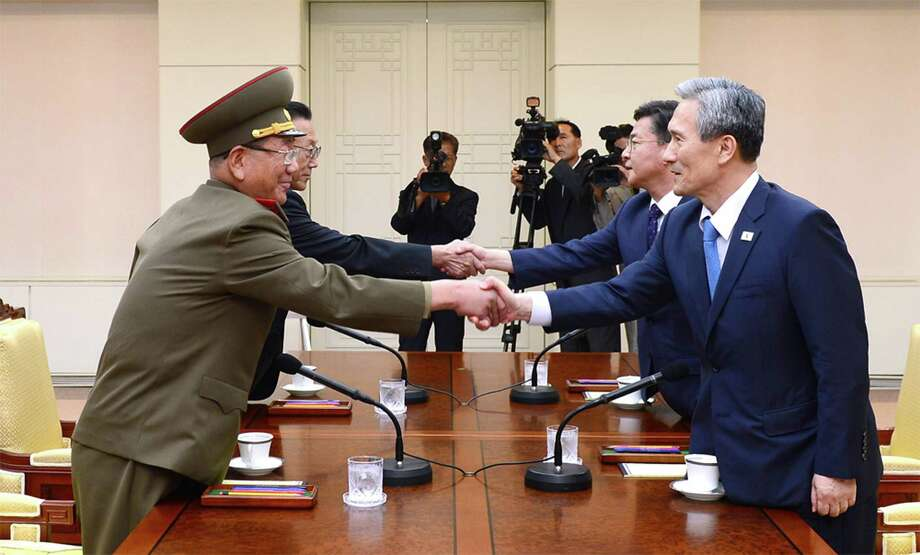 In this photo provided by the South Korean Unification Ministry, South Korean National Security Director, Kim Kwan-jin, right, and Unification Minister Hong Yong-pyo, second from right, shake hands with Hwang Pyong So, left, North Korea' top political officer for the Korean People's Army, and Kim Yang Gon, a senior North Korean official responsible for South Korean affairs, during their meeting at the border village of Panmunjom in Paju, South Korea, Saturday, Aug. 22, 2015. South Korea and North Korea agreed Saturday to hold their first high-level talks in nearly a year at a border village to defuse mounting tensions that have pushed the rivals to the brink of a possible military confrontation.  (The South Korean Unification Ministry via AP) ORG XMIT: SEL801 / The South Korean Unification Minisry