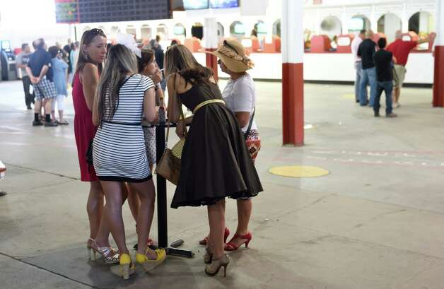 Racing patrons huddle around at table in the clubhouse trying to get their picks for an upcoming race at the Saratoga Race Course Sunday afternoon  Aug. 23, 2015 in Saratoga Springs, N.Y.      (Skip Dickstein/Times Union) Photo: SKIP DICKSTEIN