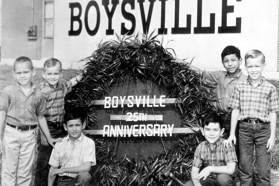 Six young boys are positioned around a sign proclaiming the 25th anniversary of Boysville in a June 12, 1968, photo.