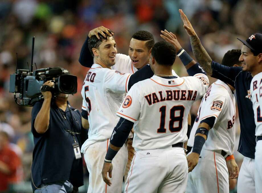 Astros catcher Jason Castro, left, is congratulated by Carlos Correa, center, and Luis Valbuena (18) after his second walkoff homer since the All-Star break. Photo: Gary Coronado, Staff / © 2015 Houston Chronicle