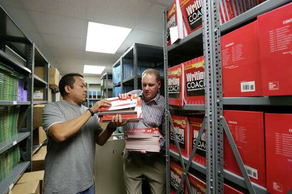 Gus Cesar, an assistant principal at Alief Middle School, helps Beau Bennet, a first-year teacher, collect textbooks. Bennett left his job in retail hoping to find something more meaningful, despite the pay cut.