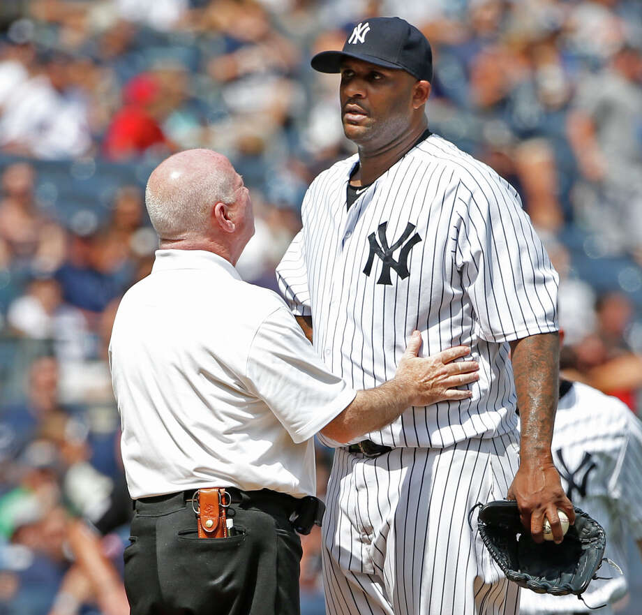 New York Yankees trainer Steve Donohue, left, talks to New York Yankees starting pitcher CC Sabathia on the mound in the third inning before New York Yankees manager Joe Girardi removed Sabathia from the baseball game against the Cleveland Indians at Yankee Stadium in New York, Sunday, Aug. 23, 2015. (AP Photo/Kathy Willens) ORG XMIT: NYY112 Photo: Kathy Willens / AP
