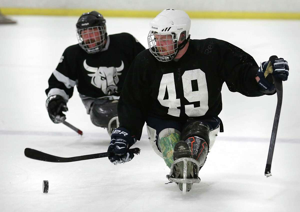 Chris Leverkuhn, right, controls the puck during a fast break during a recent practice. The San Antonio Rampage sled hockey team is made up of wounded warriors and is sponsored by the Rampage and Operation Comfort. They practiced at the Ice and Gold Center at Northwoods on Thursday, August 13, 2015.