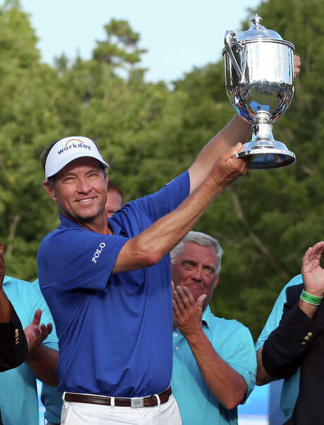 Davis Love III hoists his trophy after taking the Wyndham Championship on Sunday and becoming the third-oldest winner in PGA Tour history. Photo: Rob Brown, FRE / FR171364 AP