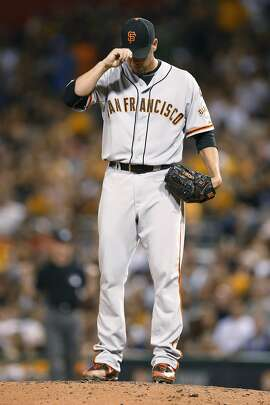 San Francisco Giants starting pitcher Ryan Vogelsong adjusts his cap after walking Pittsburgh Pirates' Jung Ho Kang with the bases loaded, scoring Starling Marte, during the first inning of a baseball game, Sunday, Aug. 23, 2015, in Pittsburgh. (AP Photo/Keith Srakocic)