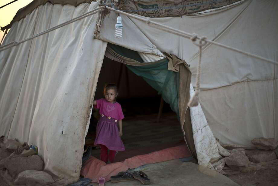 A Syrian refugee girl stands at the entrance of her family's tent at an informal tented settlement near the Syrian border on the outskirts of Mafraq, Jordan, Sunday, Aug. 23, 2015.  Photo: Muhammed Muheisen, Associated Press