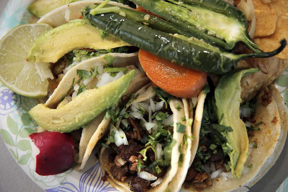El Agricultor's taco plate with al pastor and fish tacos served with a roasted serrano pepper. The truck also offers excellent shredded carnitas. Photo: Carlos Avila Gonzalez, The Chronicle