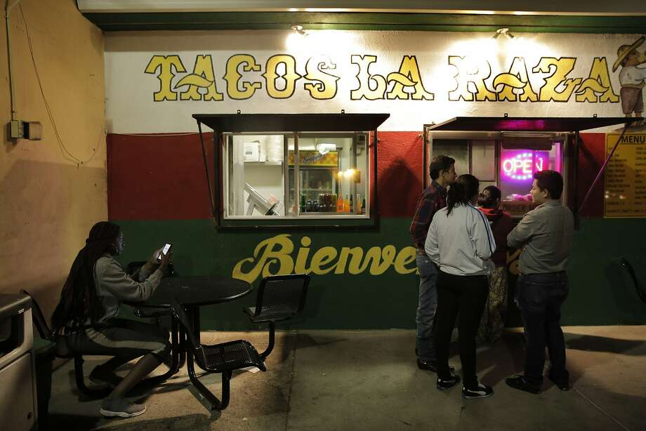 Customers wait in the parking lot for their food at Tacos La Raza in Richmond. Photo: Carlos Avila Gonzalez, The Chronicle