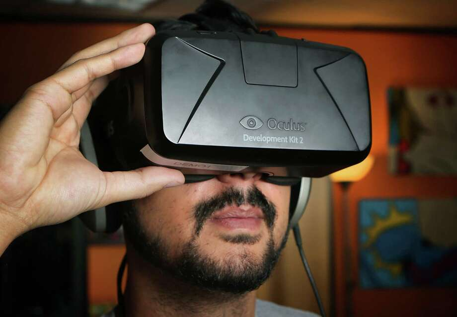 Jeremy Kenisky of Geomedia  uses a headset, goggles and earphones to view the company's virtual reality app DinoTrek VR, which transports users to a world of dinosaurs in a 360-degree environment. Photo: Bob Owen /San Antonio Express-News / San Antonio Express-News