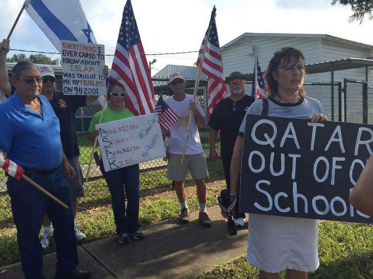 """Protesters outside the Houston ISD's Arabic Immersion Magnet School carry signs reading """"Qatar out of my school"""" and """"Everything I ever cared to know about Islam was taught to me by Muslims on 9-11-2001"""" on the first day of school, Monday, Aug. 24, 2015.  """