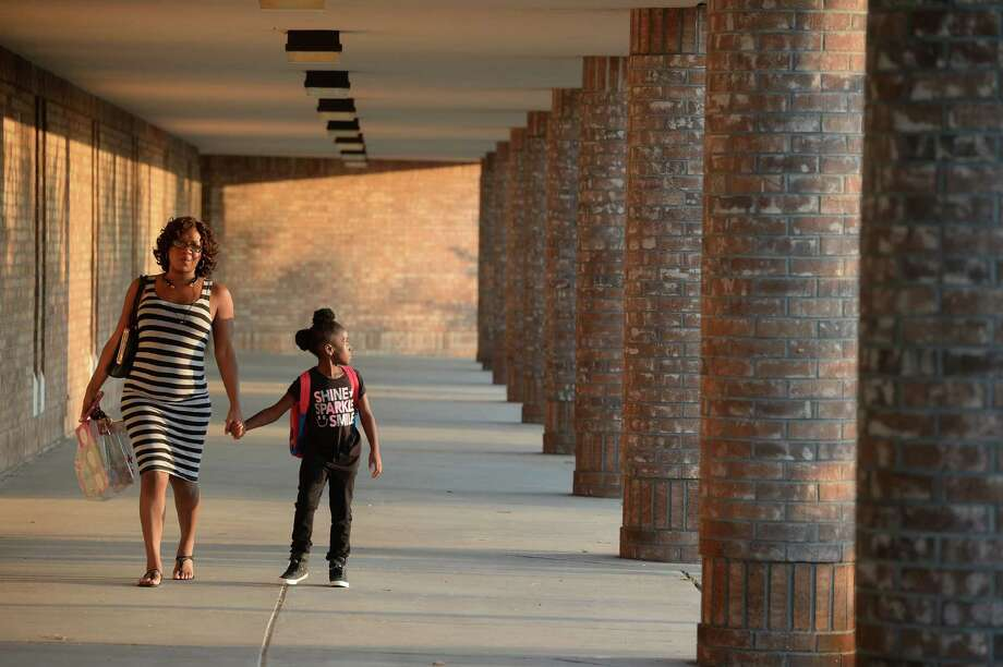 Laresha Lared walks Sanay Larden, 6, to the first day of class at Roy Guess Elementary on Monday.