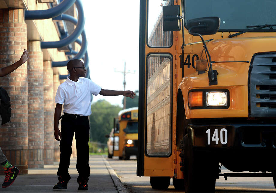 Izaiah Porter, 11, waves at passengers on a school bus at Roy Guess Elementary on Monday.  Photo taken Monday, August 24, 2015 Guiseppe Barranco/The Enterprise Photo: Guiseppe Barranco, Photo Editor