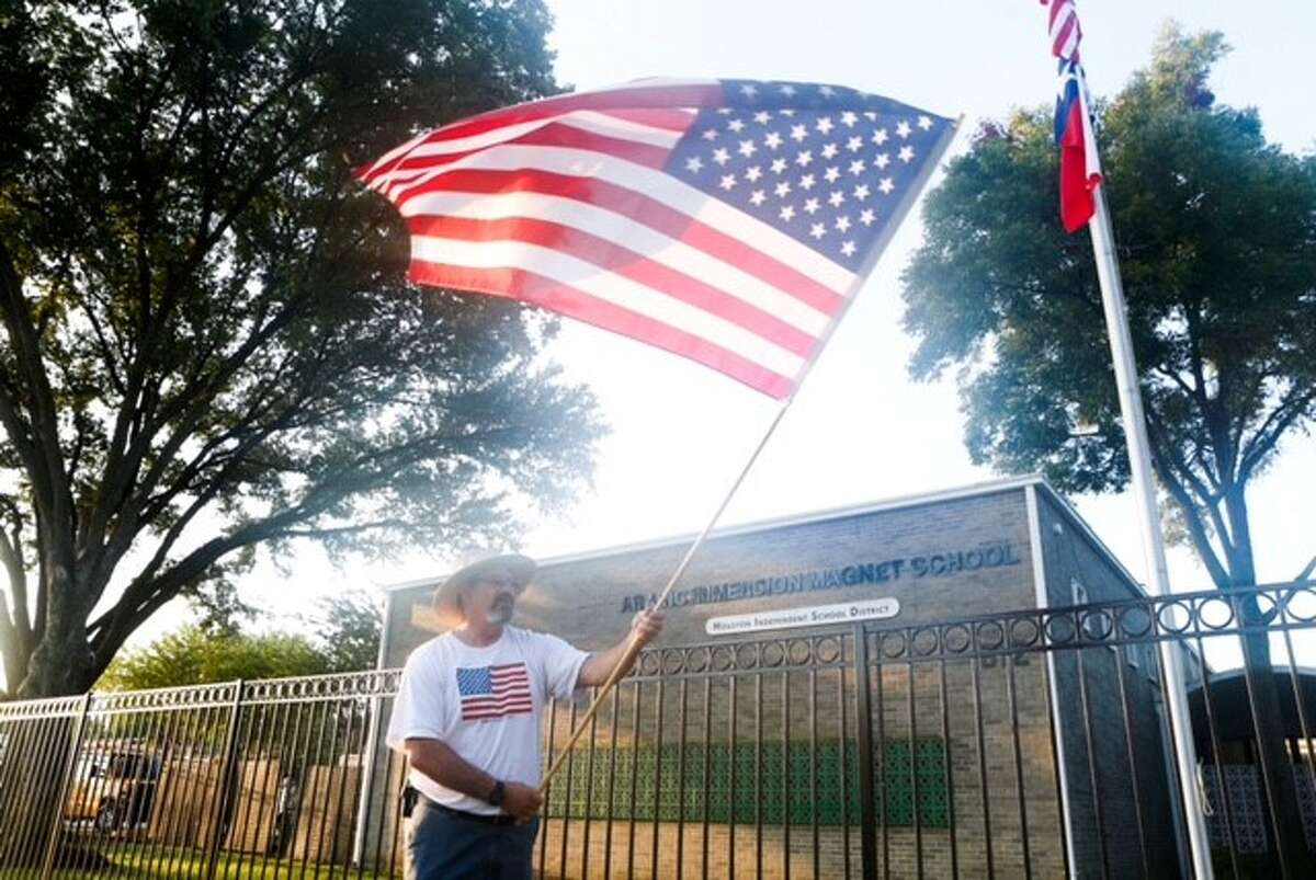 """Protesters outside the Houston ISD's Arabic Immersion Magnet School carry signs reading """"Qatar out of my school"""" and """"Everything I ever cared to know about Islam was taught to me by Muslims on 9-11-2001"""" on the first day of school, Monday, Aug. 24, 2015."""