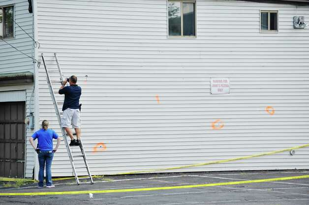 Investigators work at the scene near the corner of 112th St. and East Park Place on Monday, Aug. 24, 2015, in Troy, N.Y.  Orange paint is used by investigators to mark evidence.  Two Troy police offices, Joshua Comitale and Chad Klein were shot in this area during an incident with a suspect late Saturday night.  (Paul Buckowski / Times Union) Photo: PAUL BUCKOWSKI / 00033100A