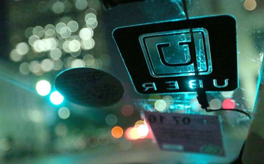 An Uber decal is seen on the windshield of Shirley Fuller's car on Aug. 7. Fuller was laid off from her job at a valve manufacturing company March 25, and is now driving for Uber to make ends meet. ( Jon Shapley / Houston Chronicle ) Photo: Jon Shapley, Houston Chronicle