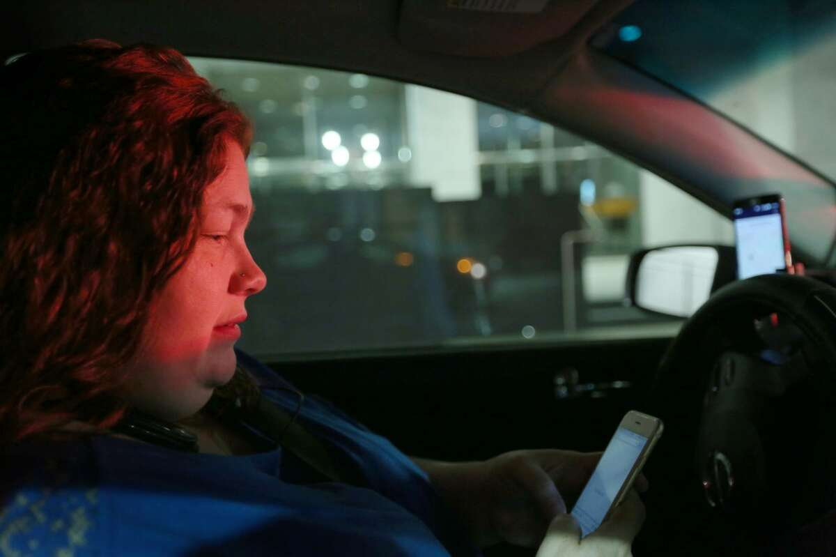 Shirley Fuller checks her Uber app for nearby riders during a shift driving for the company Friday, Aug. 7, 2015, in Houston. Fuller was laid off from her job at a valve manufacturing company March 25. She is one of a growing number of people who struggle to earn enough money as low oil prices push energy companies to lay off workers. ( Jon Shapley / Houston Chronicle )
