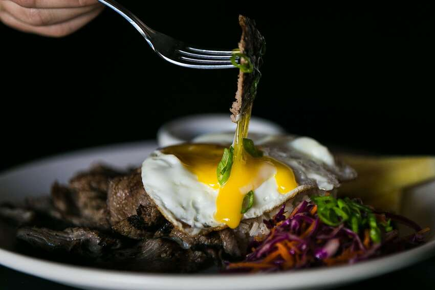 Thinly sliced top sirloin breaking into the yolk of a perfectly cooked egg at FOB Kitchen inside of Cease and Desist.