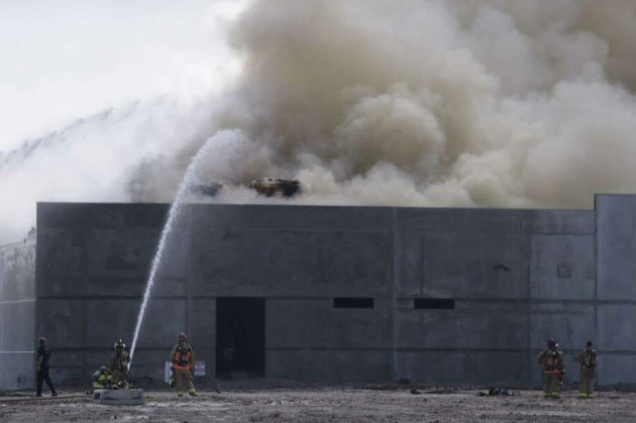 Firefighters battle a blaze at a north Houston construction site Monday, Aug. 24, 2015. Photo: Brett Coomer | Houston Chronicle