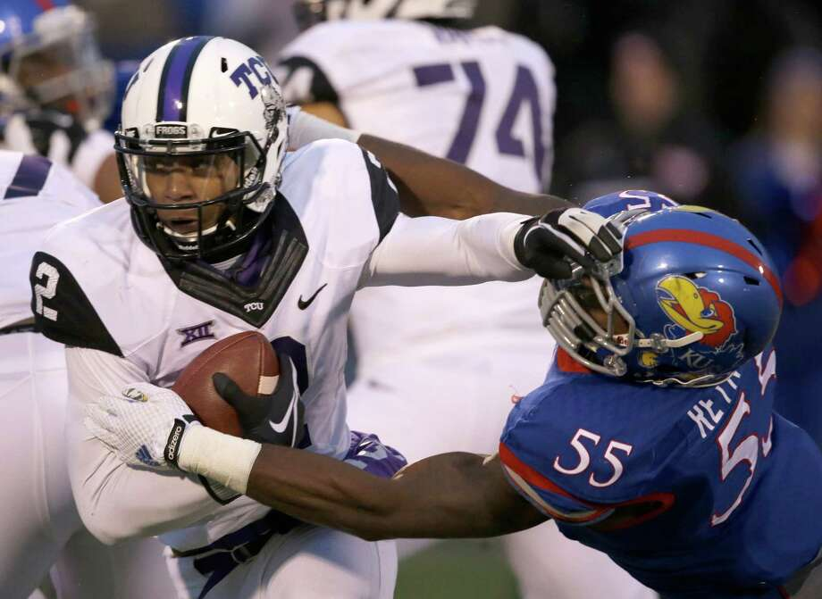 FILE - In this Nov. 15, 2014, file photo, TCU quarterback Trevone Boykin (2) avoids a tackle by Kansas linebacker Michael Reynolds (55) during the second half of an NCAA college football game in Lawrence, Kan. TCU coach Gary Patterson and Baylor coach Art Briles know a nearly-sure-fire way for their teams, and the Big 12 Conference, to avoid being left out of the College Football Playoff again. (AP Photo/Orlin Wagner, File) Photo: Orlin Wagner, STF / Associated Press / AP