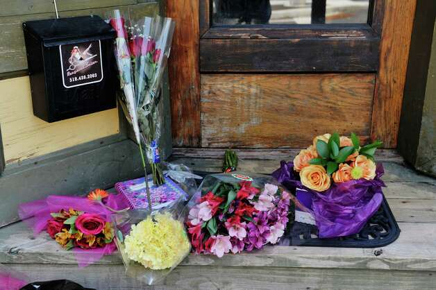 Flowers are seen at the front door of Recycled Salon on Monday, Aug. 24, 2015, in Colonie, N.Y.  Jacquelyn Porreca was stabbed inside the business last week and died from her injuries.   (Paul Buckowski / Times Union) Photo: PAUL BUCKOWSKI / 00033095A