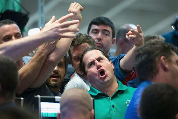 *** BESTPIX *** CHICAGO, IL - AUGUST 24:  Traders signal offers in the Standard & Poor's 500 stock index options pit at the Chicago Board Options Exchange (CBOE) on August 24, 2015 in Chicago, Illinois. Uncertainty among traders after big losses in the Asian markets caused a sharp drop in the S&P at the open.  (Photo by Scott Olson/Getty Images)