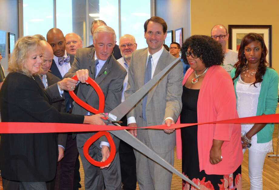 From left, Donna Paolini, general manager of Regus in Bridgeport; Bridgeort Mayor Bill Finch; U.S. Rep. Jim Himes; and Deb Caviness, director of the city's small and minority business resource office, and others cut the ribbon at Regus' new Bridgeport office on Lafayette Boulevard on Monday. Photo: Contributed Photo