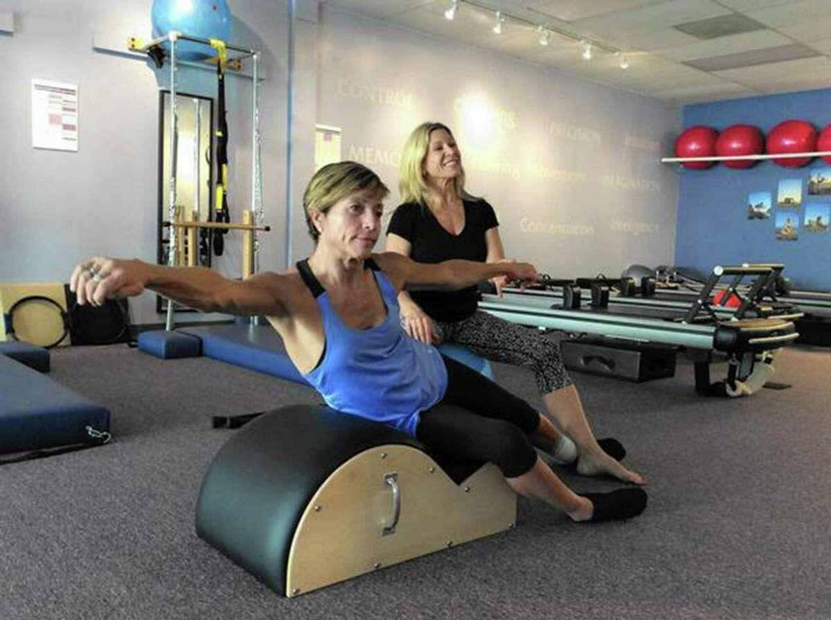 Delyn VanDyke, 52, who was injured in a motorcycle crash in 2012, works to strengthen her body with owner-trainer Tina Stathis, 48, at Tru Pilates and Yoga Studio in Altamonte Springs, Fla.