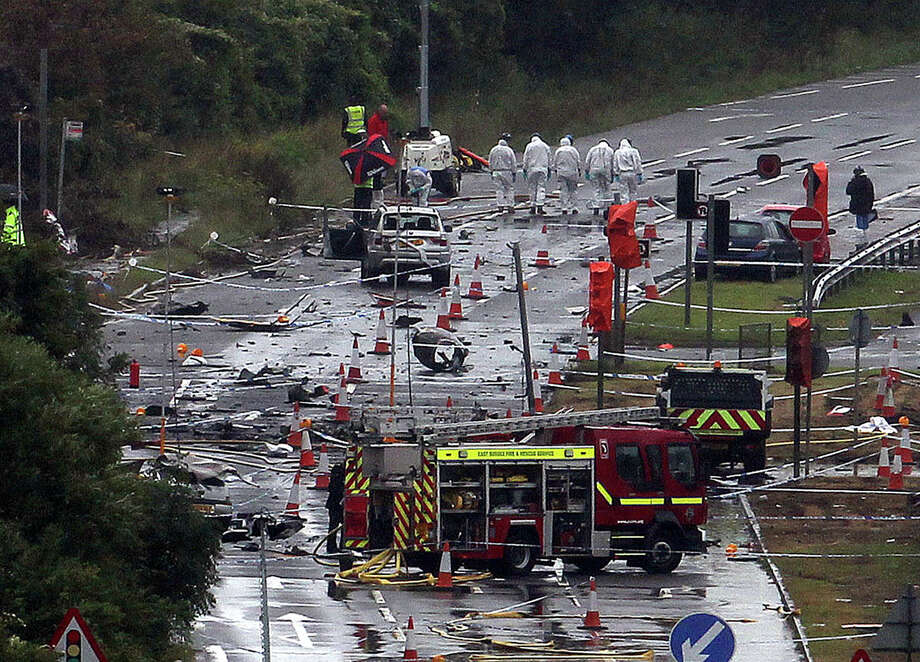 Emergency services workers on Monday clean up the scene of Saturday's air show crash of a vintage Hawker Hunter jet on a highway near Shoreham in southeastern England. Police expect the death toll of 11 to climb. Photo: Steve Parsons, SUB / PA