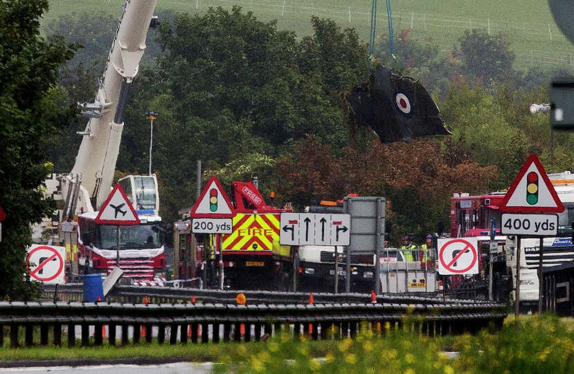 A crane lifts a section of the Hawker Hunter jet that crashed into a highway Saturday after it faile