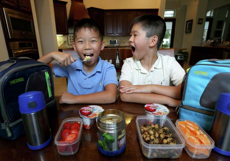 Macaroni and cheese suits Cornerstone Elementary third-grader Ethan Liaw, left. His brother William, a fifth-grader, prefers to open wide for chickpea salad. Yogurt and fresh fruit are in the mix for both Sugar Land boys. Photo: Gary Coronado, Staff / © 2015 Houston Chronicle