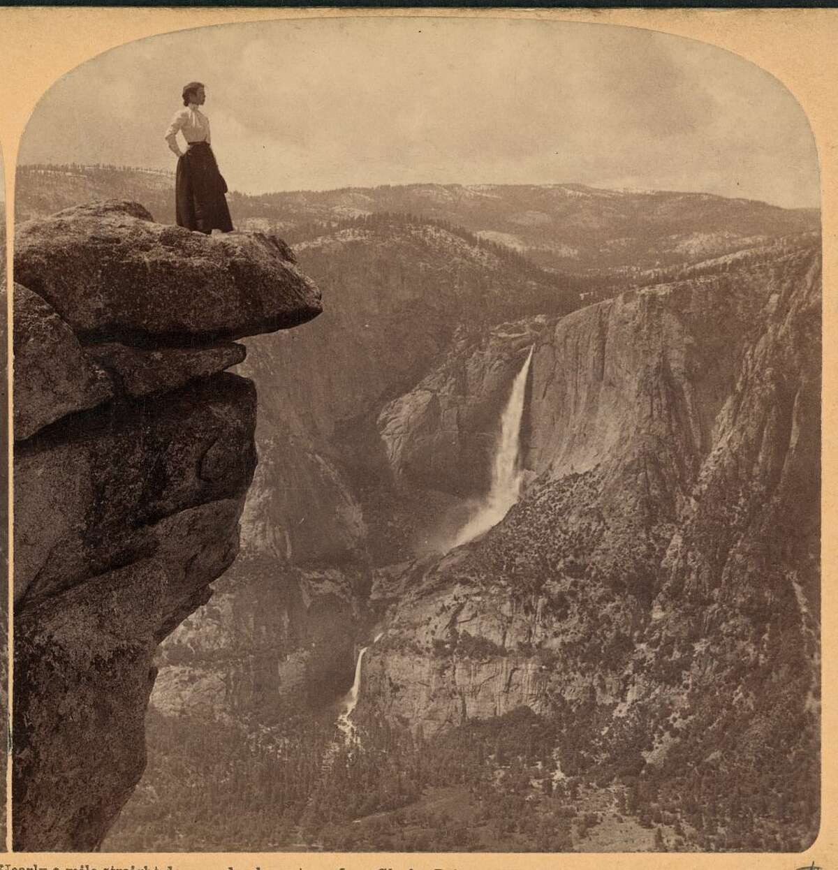 HISTORIC PHOTOS OF YOSEMITE NATIONAL PARK A woman stands on the precipice looking out onto the valley. The striking photograph was taken in 1902.