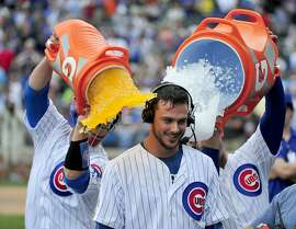 CHICAGO, IL - AUGUST 24: Kris Bryant (C) of the Chicago Cubs gets gets a gatorade bath from David Ross (L) and Anthony Rizzo (R) after hitting a walk-off home run against the Cleveland Indians during the ninth inning on August 24, 2015 at Wrigley Field in Chicago, Illinois. The Cubs won 2-1.(Photo by David Banks/Getty Images)