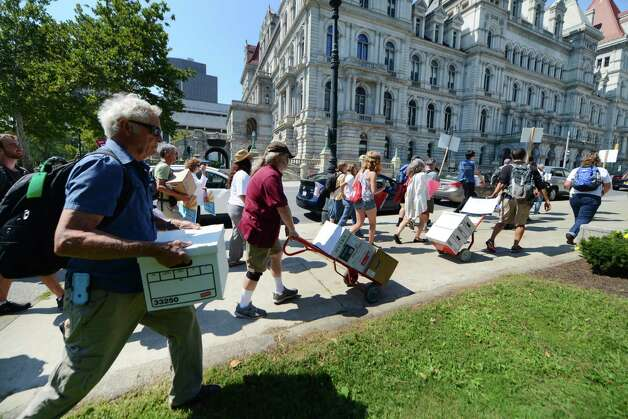 Demonstrators against a proposed bailout of the Cayuga Coal Plant march to the Capitol to deliver more than 14,000 comments to Gov. Cuomo and his Public Service Commission urging them to deny the bailout Monday, Aug. 24, 2015, in Albany, N.Y. According to the Sierra Club, the Cayuga Coal Plant receives subsidies of approximately $4 million a month and is requesting that electricity customers spend another $145 million to help the plant for another ten years. (Will Waldron/Times Union) Photo: WW