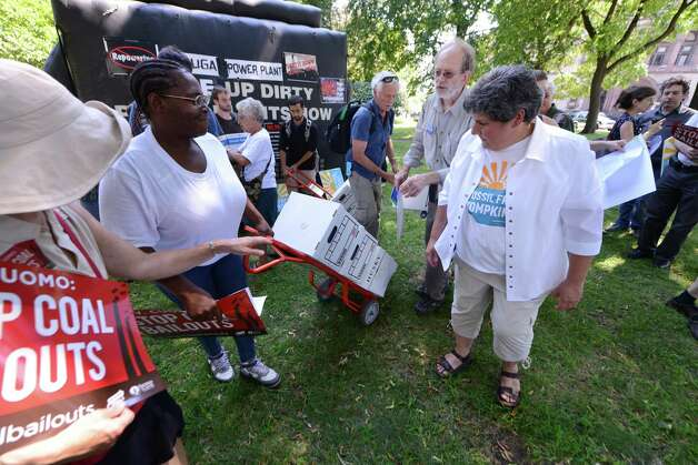 Town of Caroline Councilmember, Irene Weiser, right, joined demonstrators in delivering more than 14,000 comments to Gov. Cuomo and his Public Service Commission urging them to deny a proposed bailout of the Cayuga Coal Plant Monday, Aug. 24, 2015, at Academy Park in Albany, N.Y. According to the Sierra Club, the Cayuga Coal Plant receives subsidies of approximately $4 million a month and is requesting that electricity customers spend another $145 million to help the plant for another ten years. (Will Waldron/Times Union) Photo: WW