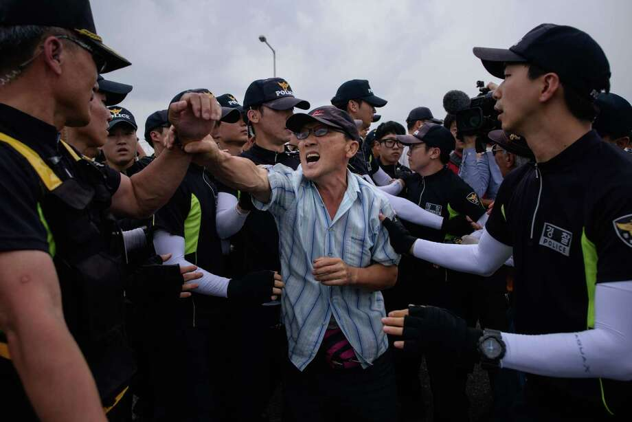 Anti-North Korean activists struggle with police on the Unification Bridge that leads to the Demilitarized Zone between North and South Korea in Paju on Tuesday. South Korea's president demanded an apology for recent provocations. Photo: ED JONES, Staff / AFP
