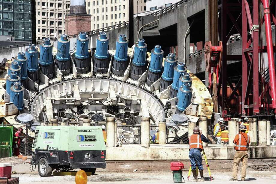 Crews worked Monday, Aug. 24, 2015 to begin one of four crane operations to lower Bertha's cutter head and drive unit back into the ground. Once the giant tunnel boring machine is back together and tested, it will start tunneling again Nov. 23, nearly two years after it stopped 1,000 feet into the nearly two-mile tunnel project. Photo: DANIEL DEMAY/SEATTLEPI.COM
