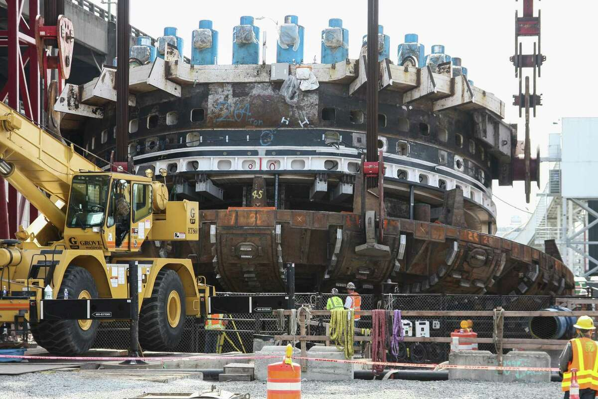 The cutter head and drive unit for Bertha (pictured) weigh about 4 million pounds, according to Washington Departnent of Transportation officials. The lower section in this image is the upgraded cutter head, which Seattle Tunnel Partners expects to perform better and make it through the rest of the dig. Crews worked Monday, Aug. 24, 2015 to begin one of four crane operations to lower the giant tunnel boring machine's cutter head and drive unit back into the ground. Once the giant tunnel boring machine is back together and tested, it will start tunneling again Nov. 23, nearly two years after it stopped 1,000 feet into the nearly two-mile tunnel project.