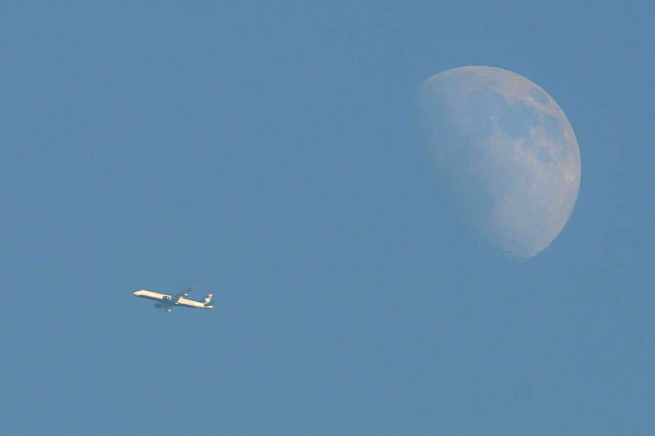 A commercial airplane can be seen next to the moon above Stamford, Conn., on Monday, Aug. 24, 2015. Photo: Jason Rearick / Hearst Connecticut Media / Stamford Advocate