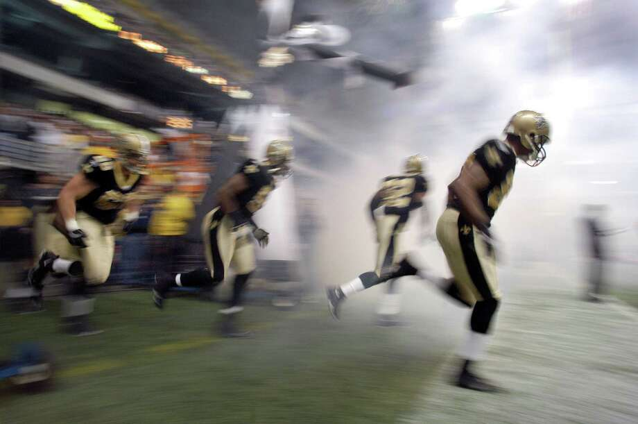 The New Orleans Saints take the field before a game between the New Orleans Saints and the Detroit Lions at the Alamodome, Dec. 24, 2005. The Saints were defeated 13-12. Photo: Express-News File Photo / SAN ANTONIO EXPRESS-NEWS