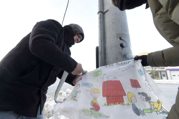 Rocco Bruno, left, adds to a memorial on Friday, Feb. 13, 2015, at Quail Street and Central Avenue in Albany where a 4-year-old child was killed Thursday. (Skip Dickstein/Times Union)