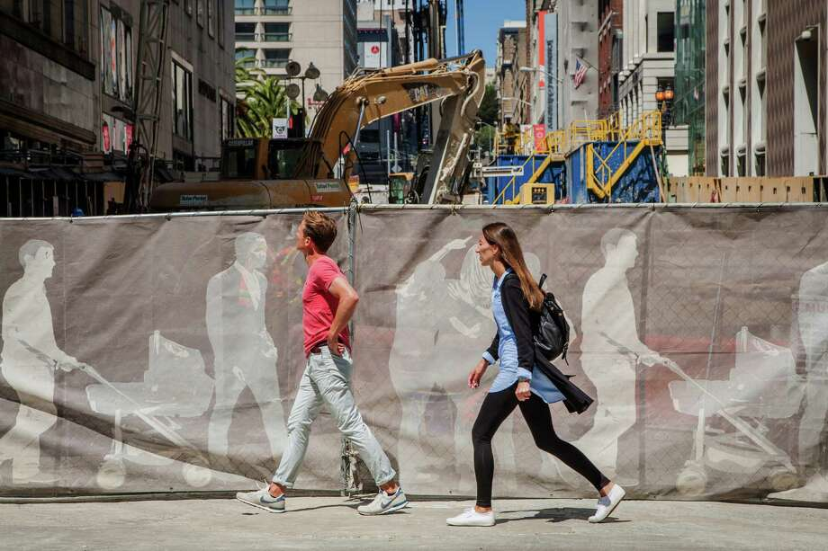 Bjoern Hoppe, left, and Viviene Vehar walk past construction along O'Farrell Street, Monday, Aug. 24, 2015, in San Francisco, Calif. Store owner Gary Champagne, who owns a nearby beauty supply store, said his business plummeted when the Central Subway project began in 2012. He said his store Beauty Land may not survive much longer. Because of construction, vehicles aren't allowed to park near his business and the construction vehicles that are allowed are blocking the view of the front of the store. Photo: Santiago Mejia / Special To The Chronicle / ONLINE_YES