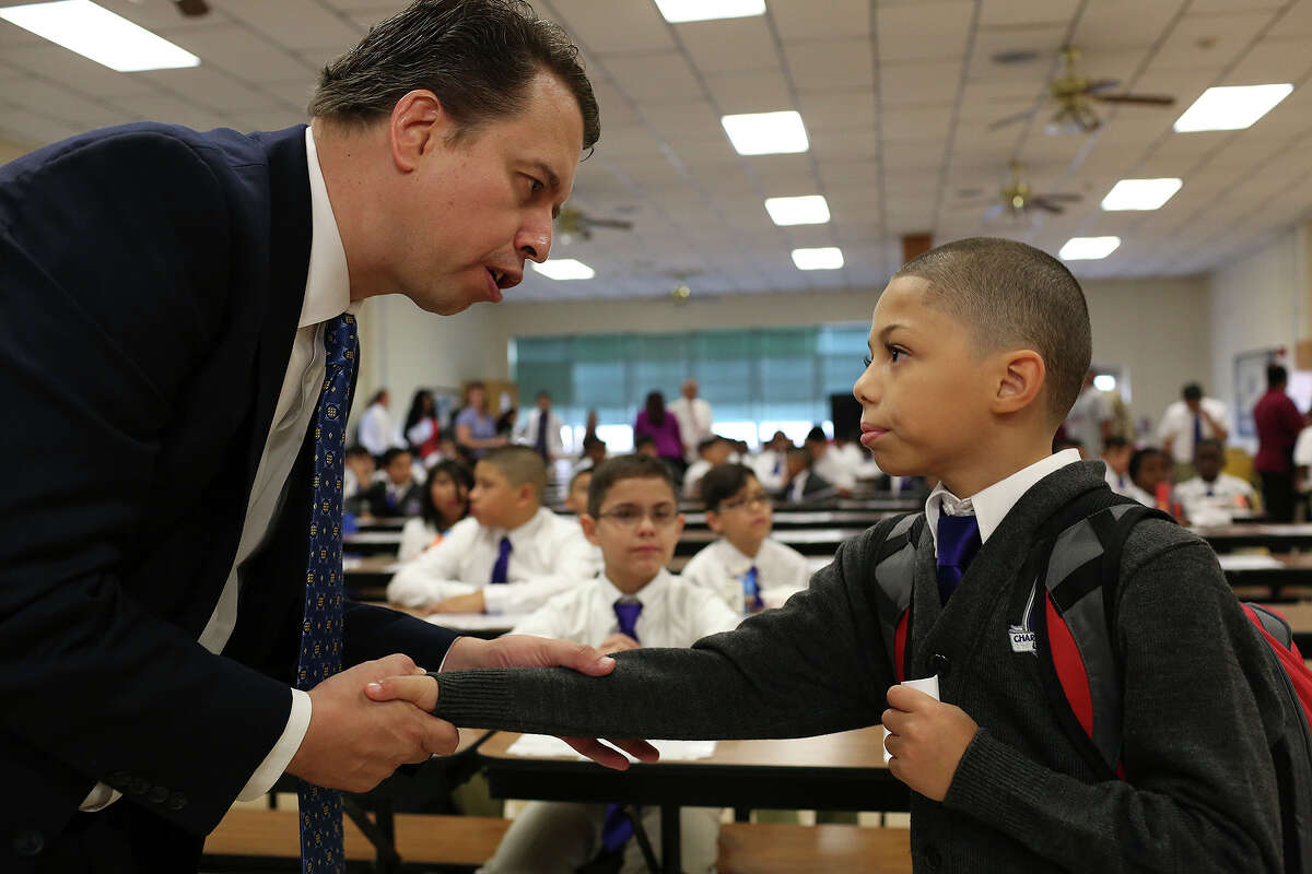San Antonio Independent School District Superintendent Pedro Martinez talks on Aug. 24 with fourth grader Nathan Sutherland-Trevino, 9, before the opening assembly on the first day of the Young Men's Leadership Academy, San Antonio's first public all-boys school. The district's population has many underlying socioeconomic woes but such programs are needed to help students overcome such challenges.