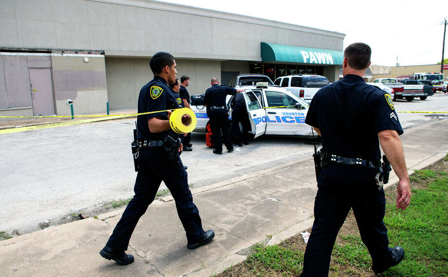Houston Police officers investigate the scene after an attempted robbery at Diamond Pawn in northeast Houston. One suspected robber was fatally shot by the shop owner. Two others were arrested and police are seeking a third. Photo: Cody Duty, Staff / © 2015 Houston Chronicle