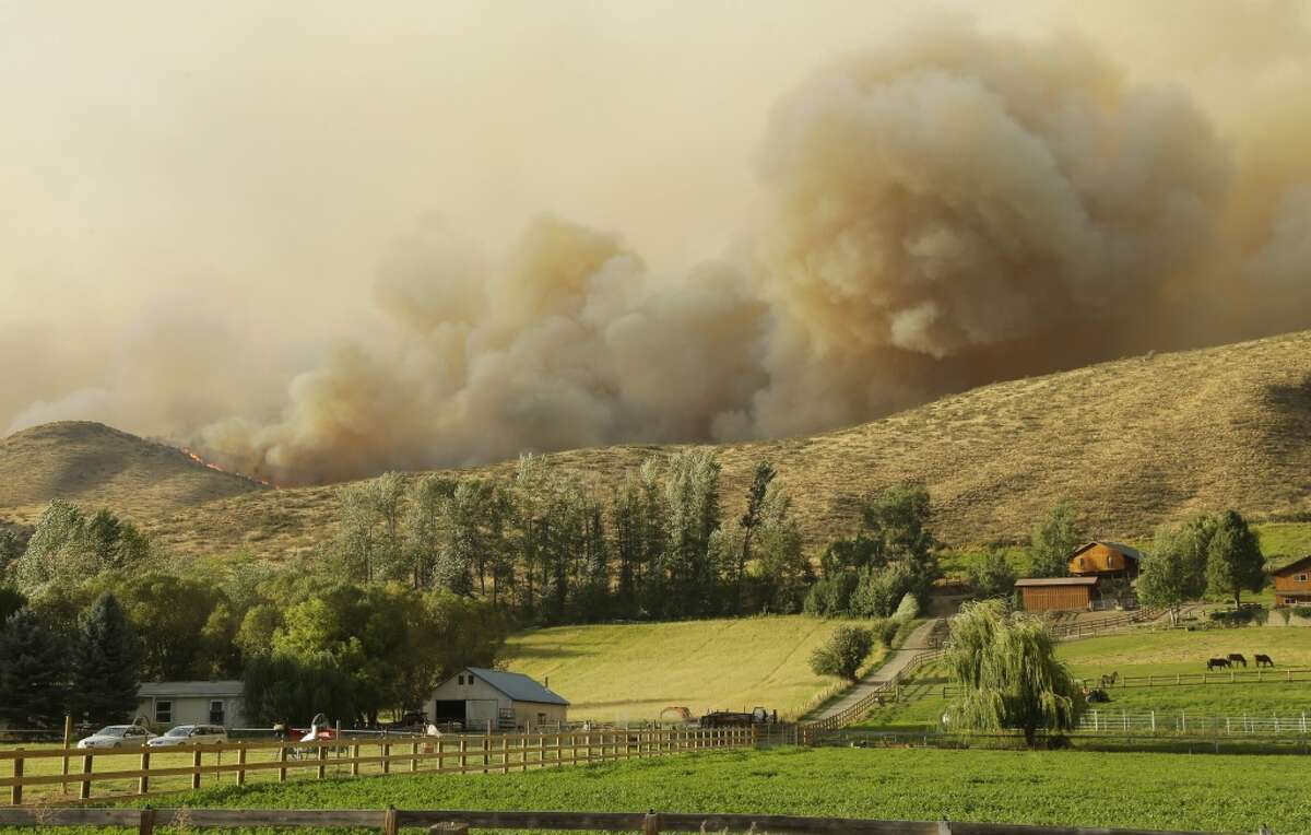 Flames and smoke rise on a hillside above homes on Twisp River Road near Twisp, Wash., Wednesday, Aug. 19, 2015.