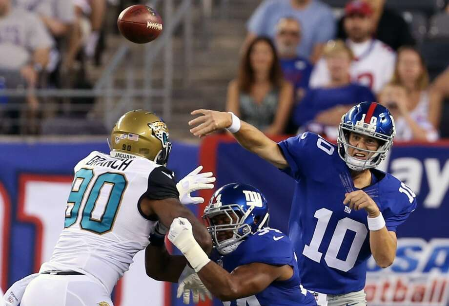 New York Giants quarterback Eli Manning (10) throws a pass over Jacksonville Jaguars' Andre Branch (90) during the first half of a preseason NFL football game Saturday, Aug. 22, 2015, in East Rutherford, N.J. (AP Photo/Adam Hunger) ORG XMIT: ERU116 Photo: Adam Hunger / FR110666 AP