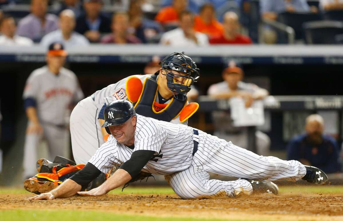 NEW YORK, NY - AUGUST 24: Brian McCann #34 of the New York Yankees is tagged out at home trying to tag up in the the seventh inning by Hank Conger #16 of the Houston Astros at Yankee Stadium on August 24, 2015 in the Bronx borough of New York City. (Photo by Jim McIsaac/Getty Images)